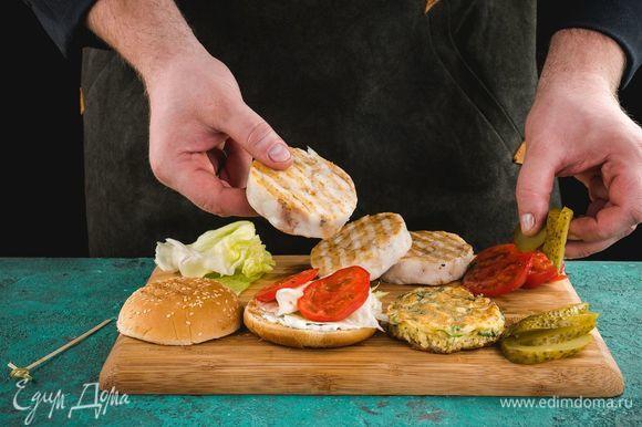 Смажьте одну часть булочки соусом и соберите бургер. На соус выложите листья салата, сверху — обжаренную рыбу. Затем положите нарезанные кружками помидоры и соленые огурцы.