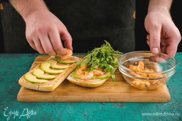 Соберите брускетту: на подсушенную чиабатту выложите соус, авокадо, креветки и руколу.