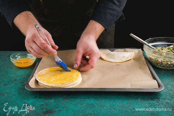 Выложите заготовки на противень, смажьте желтком.