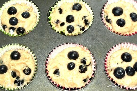 В формы для кексов ставим бумажную формочку и выкладываем в нее тесто. Сверху на тесто добавить несколько ягод голубики. Отправляем в духовку на 20 минут (ориентироваться на свою духовку). Готовность проверить бамбуковой палочкой.