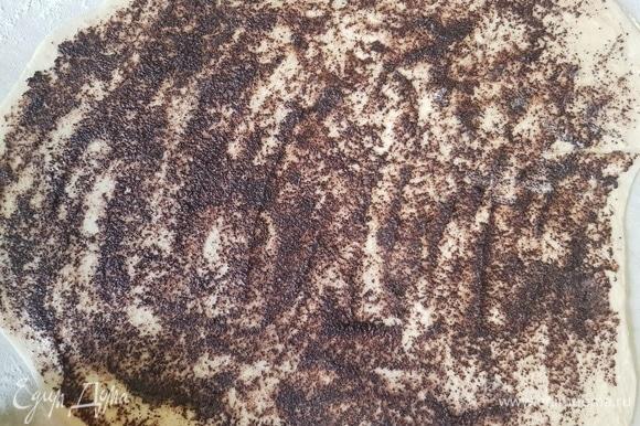 Одну часть выложить на посыпанную мукой поверхность и раскатать прямоугольник. Смазать сначала половиной растопленного сливочного масла, потом — половиной маковой начинки.