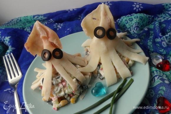 Разложить салат и украсить кальмаром, уложив его сверху. Сделать глазки из маслин. Вот такая веселая семейка кальмарчиков получилась.