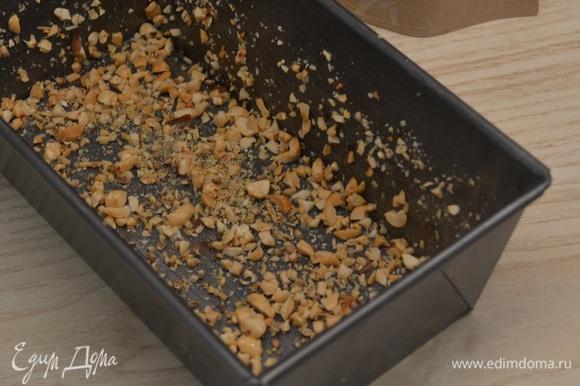 Арахис мелко порубить. Форму смазать маслом и обильно посыпать арахисом.