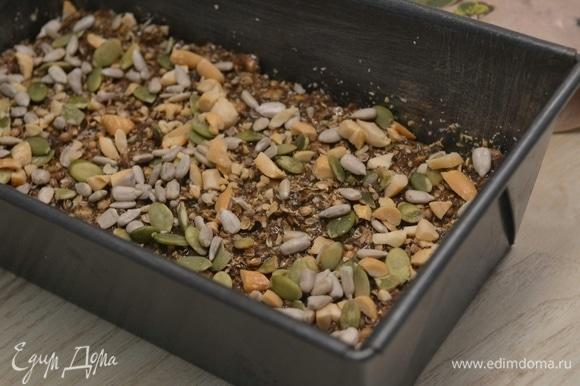 Выложить тесто в форму, сверху посыпать орехами, тыквенными семечками и кориандром. Выпекать 30–35 минут при 175°C.