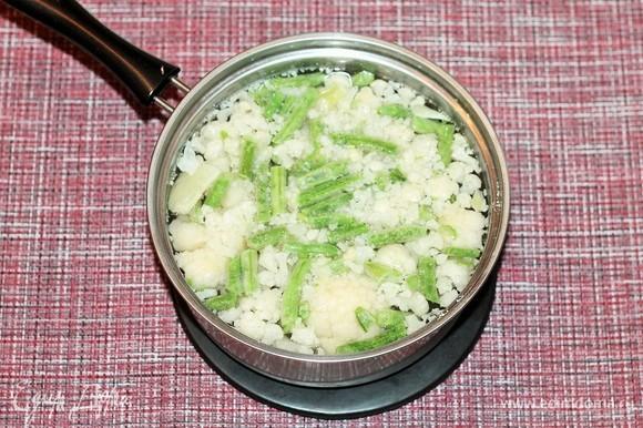 Цветную капусту разберите на соцветия и добавьте в кипящую воду. Сюда же добавьте стручковую фасоль, 1–2 минуты бланшируйте. Затем слейте воду через сито.
