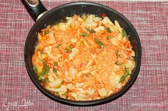 Влейте 250 мл овощного бульона, всыпьте чечевицу и перемешайте, накройте сковороду (или кастрюлю) крышкой и тушите до готовности на слабом огне.
