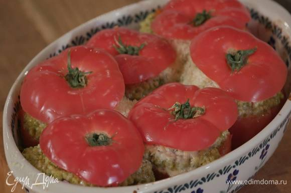 Запекать помидоры в разогретой духовке 20‒25 минут, затем накрыть «крышечками» и запекать еще несколько минут до готовности.