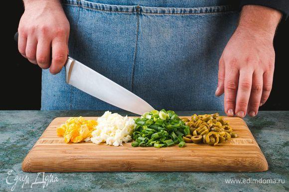 Яйца отварите вкрутую. Остудите и очистите. Нарежьте крупно зеленый лук, оливки. Белки и желтки нарежьте по отдельности.