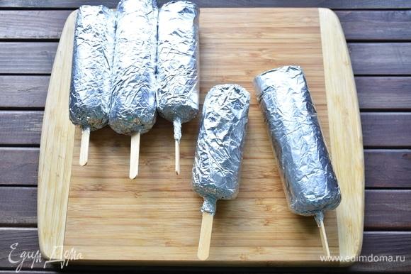 Куриный рулет вместе со вставленной палочкой завернуть плотно в фольгу. Внизу края фольги закрепить вокруг палочки. Заготовки «эскимо» готовы. Их можно взять с собой и запечь на углях. А можно поместить в пакет для запекания, влить немного воды (1 ст. л.) и запечь в духовке при 200°C 40 минут.