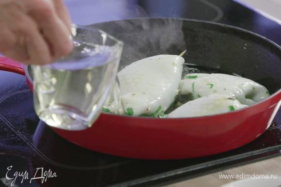 Добавить в сковороду белое вино, накрыть ее крышкой, убавить огонь и томить кальмары 15–20 минут.