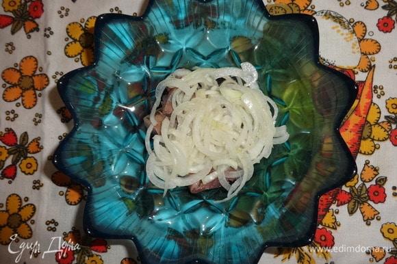 С лука слить маринад, выложить часть лука на селедку.