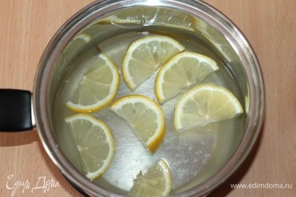 Из воды (1 литр) и сахара сварить сироп, постоянно помешивая. В кипящий сироп выложить дольки лимона и снять с огня.