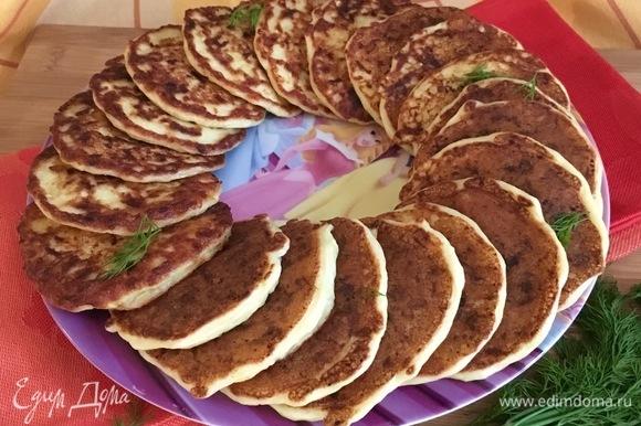 Выложить оладьи на блюдо по кругу, оставив серединку для соусника.
