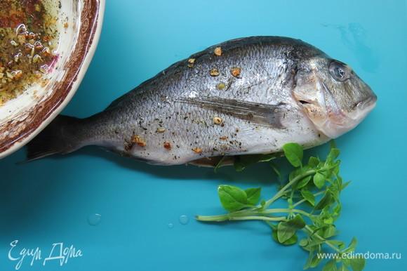 У рыбы удалить жабры и внутренности из брюшка, натереть полученным маринадом снаружи и внутри. В брюшко вложить дольку лайма и веточку базилика. Оставить на полчаса.