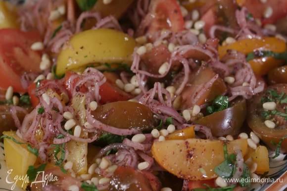 Помидоры посыпать нарезанным базиликом, полить оставшимся оливковым маслом, посолить, поперчить, сверху разложить лук со специями, посыпать салат кедровыми орехами.