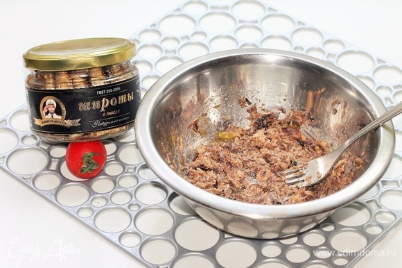 Со шпрот ТМ «Капитан Вкусов» слить масло, выложить их в миску, размять вилкой.