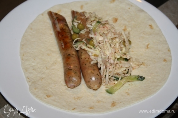 Колбаски разрезать пополам, выложить на тортильи, добавив капустный салат.