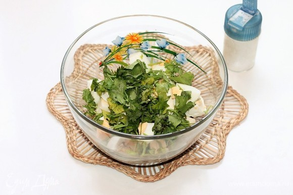 Кинзу вымыть, обсушить бумажным полотенцем и нарезать. Добавляем в миску сваренные вкрутую, очищенные и порубленные яйца, зелень, домашний майонез и кетчуп. Можно добавить прессованный зубчик чеснока (по желанию).