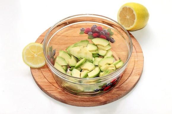 Авокадо очищаем от шкурки, нарезаем дольками и сбрызгиваем лимонным соком.