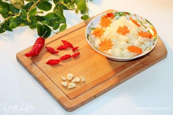 Острый перец и чеснок нарезать кружочками. Картофель — кубиками.