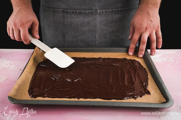 Противень застелите пергаментом, выложите на него тонким слоем массу. Выпекайте основу при 190°С в течение 6 минут. Готовый корж остудите и вырежьте три одинаковых части по размеру формы, в которой будете собирать торт, остатки коржа разломайте на маленькие кусочки.