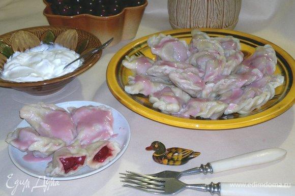 Готовые вареники с вишнями выложить на блюдо, полить соусом. Сметану с сахаром подать отдельно. Угощайтесь! Приятного аппетита!