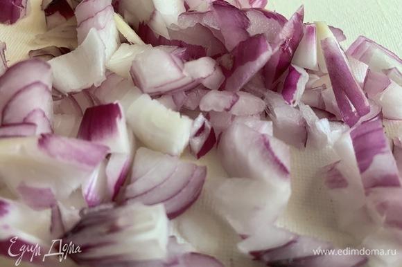 Нарежьте мелко красный лук. На разогретую сковороду налейте масло и жарьте лук 2 минуты до прозрачности.