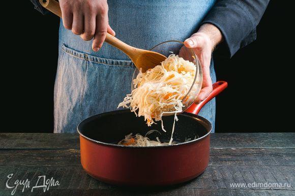 При необходимости слегка промойте квашеную капусту, отожмите. Добавьте капусту в сковороду к луку.