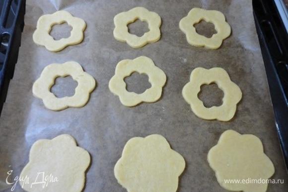Перенесите их на противень, выстланный пекарской бумагой, и у половины заготовок вырежьте небольшое отверстие цветочком, звездочкой или просто кружочком. Выпекайте 10–15 минут, ориентируйтесь по своей духовке.