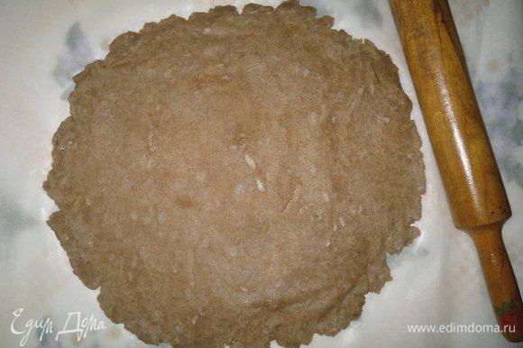 Достать тесто из холодильника. Выложить на пекарскую бумагу и раскатать в круг толщиной 0,5 см. Вместе с бумагой перенести круг теста на противень.