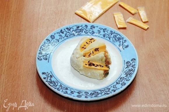 Украшаем заготовки булочек полосками плавленого сыра и посыпаем тмином. Плавленый сыр можно заменить на тертый твердый сыр, а тмин — на черный кунжут. Но тмин очень ароматный.