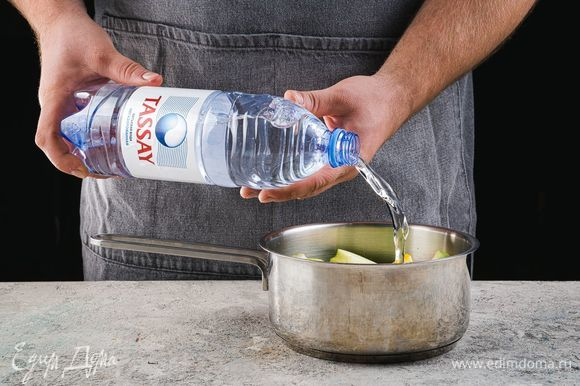 Выложите яблоки и кусочки лимона в кастрюлю, залейте негазированной водой Tassay так, чтобы вода накрывала фрукты.
