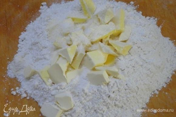 Для теста муку просеять горкой на рабочую поверхность, сделать углубление и положить туда 100 г охлажденного сливочного масла, нарезанного кубиками. Добавить соль и сахар. Все мелко порубить, чтобы получилась маслянистая крошка.
