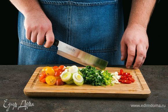 Чеснок мелко нарежьте, лук-порей и чили нарежьте кольцами, помидоры — пополам.