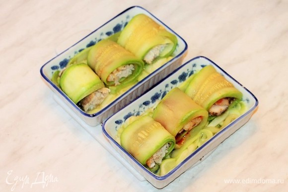 Смазать формочки растительным маслом и выложить в начале тонко нарезанный кабачок, а сверху разложить рулетики.