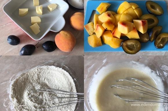 Духовку нагреть до 180°C. Персики очистить и крупно нарезать. Сливы разделить пополам и извлечь косточки. В форму для выпечки положить масло и отправить в духовку на 5–7 минут. В миске смешать муку, соль, ванильный сахар, разрыхлитель и сахар. Затем добавить молоко и хорошо перемешать венчиком.