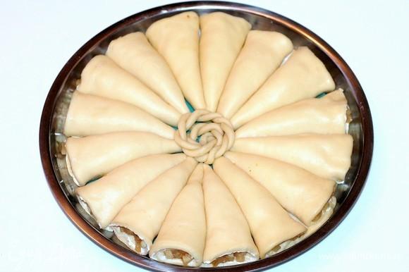 Берем форму для выпечки диаметром 26 см и застилаем пекарской бумагой или силиконовым ковриком. Смазываем холодным сливочным маслом. Выкладываем заготовки по кругу.
