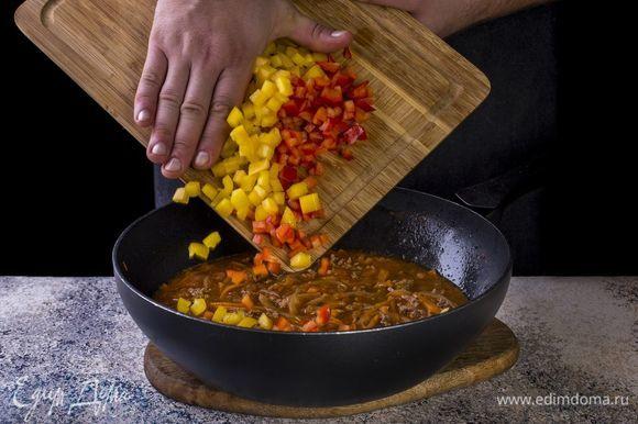 Перцы нарежьте мелкими кубиками, добавьте в сковороду.