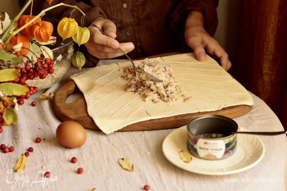 Делаем продольные надрезы, начиная от того места, где будет заканчиваться начинка. Выкладываем в центр начинку. Для сочности можно добавить сливочное масло. Затем каждую полоску попеременно укладываем на пирог по типу косички.