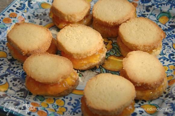 Смазать одно готовое печенье апельсиновым джемом и накрыть вторым.