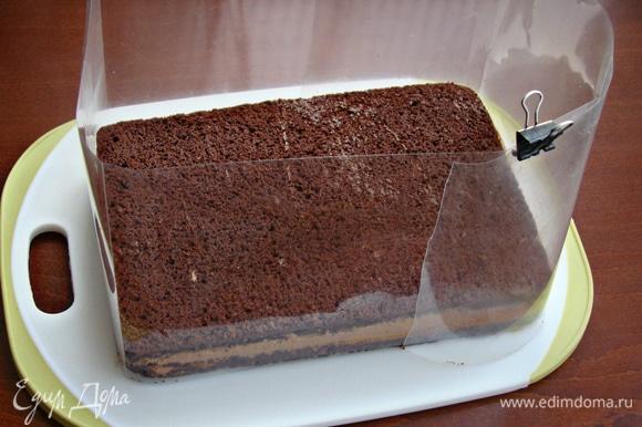Бисквит разрезать на два коржа, промазать остывшим заварным шоколадным кремом Haas. Так как у меня форма для выпечки не разъемная, я сделала импровизированные бортики из ацетатной пленки. Торт поставить в холодильник примерно на полчаса, чтобы схватился крем.