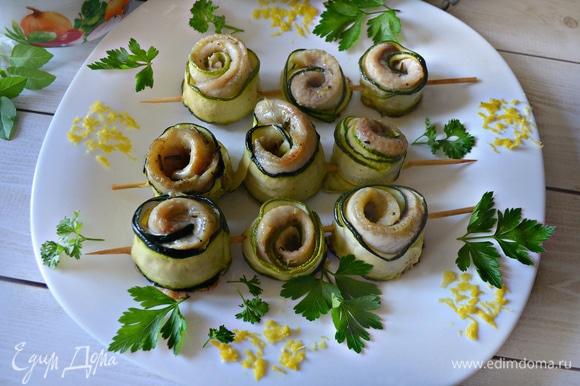 Готовые шпажки выложите на блюдо, украсьте зеленью петрушки и цедрой лимона.