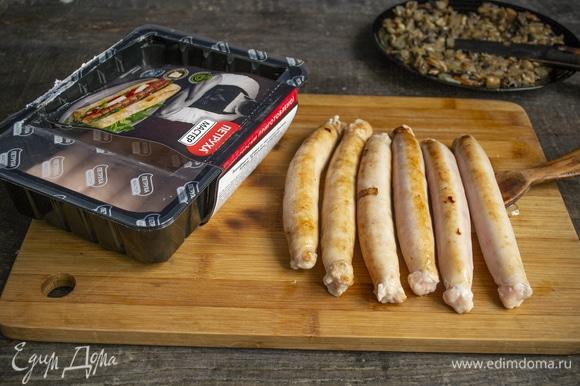 На разогретую сковороду выкладываем 6 куриных колбасок, обжариваем по 2 минуты с каждой стороны.