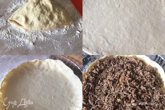 Духовку разогреть до 180°C. Тесто достать из холодильника, рабочую поверхность присыпать мукой и разделить тесто на две части. Раскатать одну часть, переложить в форму, распределить мясную начинку.