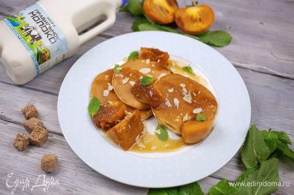 Выложите на тарелку готовые оладьи с обжаренной хурмой. Подавайте, украсив мятой.
