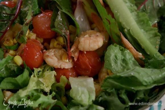 Горячие креветки и салатный микс выложить на блюдо с овощами, все перемешать и полить заправкой.