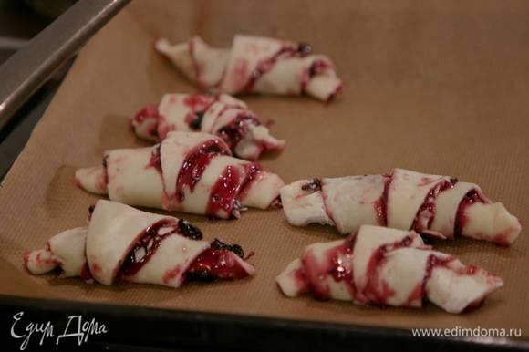 Выложить рогалики на противень, выстеленный бумагой для выпечки.