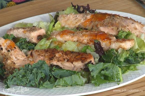 Салат переложить на тарелку, сверху выложить рыбу, полить острым соусом.