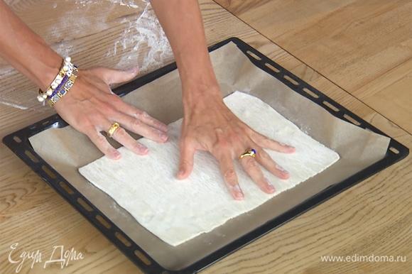 Раскатать тесто, на четверть увеличив его в размере. Выложить на противень, застеленный бумагой для выпечки.