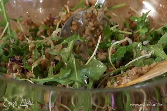 Отваренную гречку, обжаренный лук с чесноком, проростки и руколу выложить в салатницу, полить заправкой и перемешать.